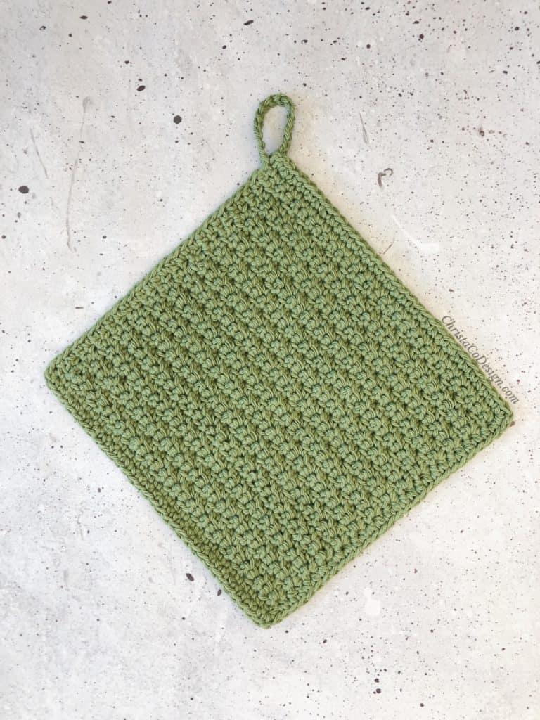 Crochet dishcloth in green with hanging loop.