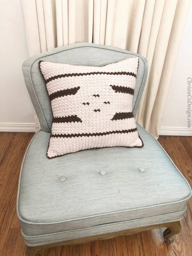 White crochet pillow with contrasting dark stripes on chair.