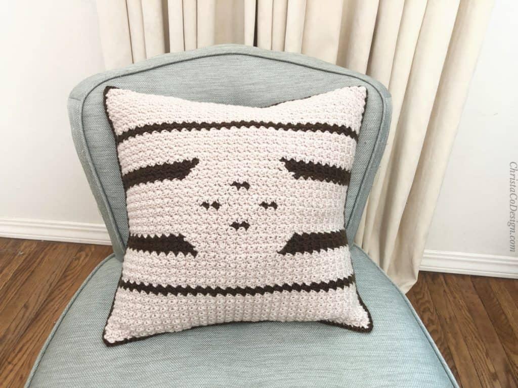 Light side with dark stripes crochet pillow on blue chair.