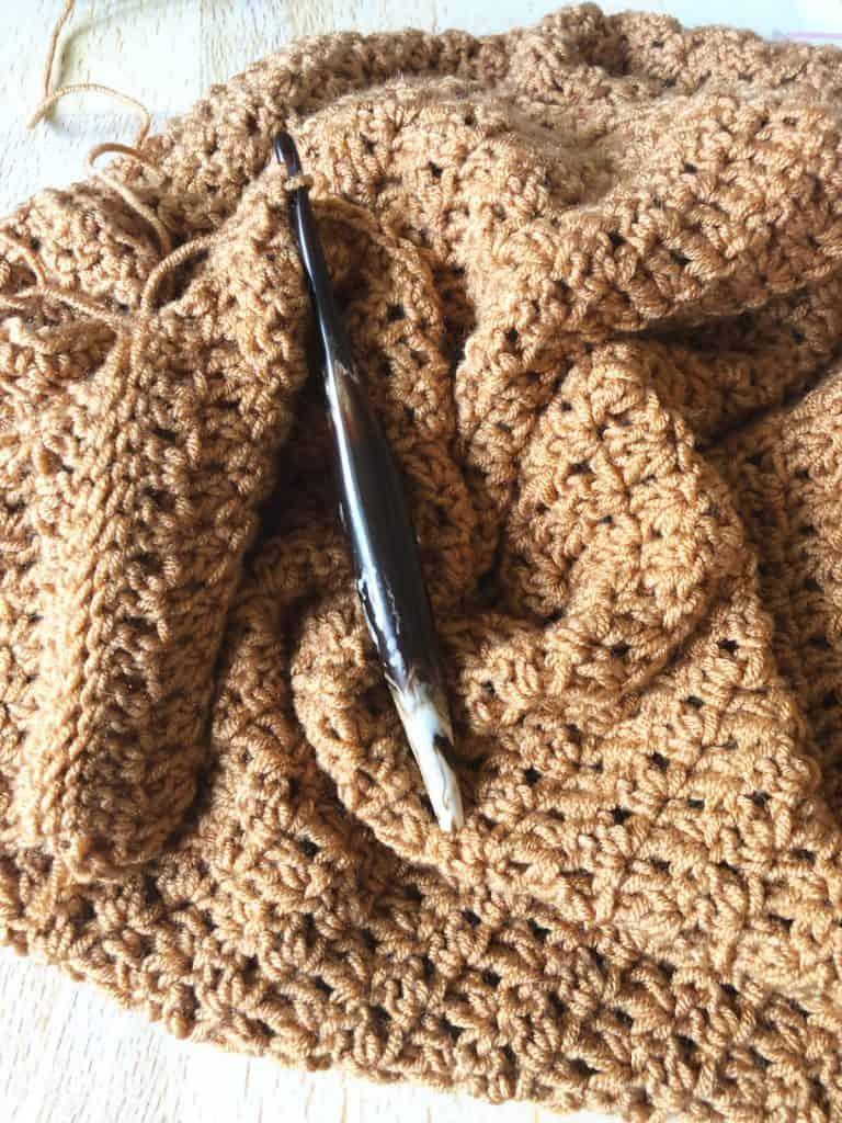 Crochet hook in cafe and sweater in progress.
