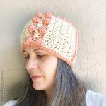 Bobble stitch earwarmer on woman in beige and peach.