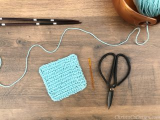 Knit scrubby with needles and scissors in blue cotton yarn.