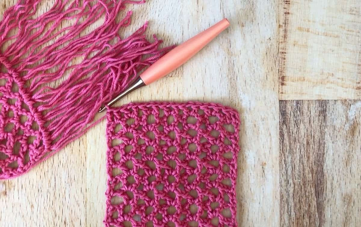 Pink lacy crochet scarf with fringe.