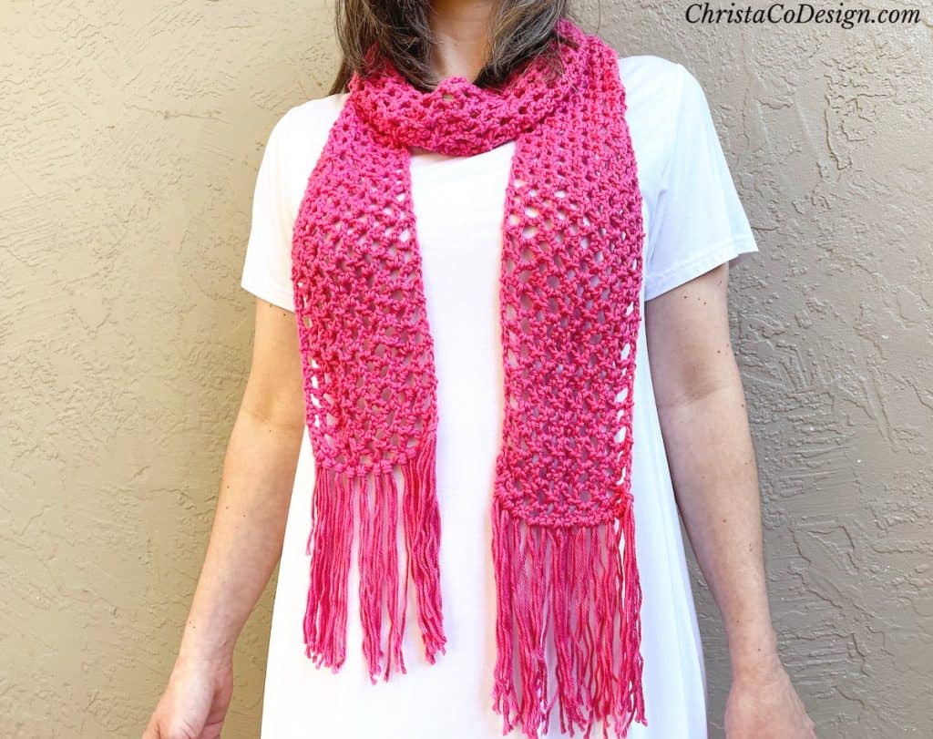 Woman in white dress with pick lacy crochet scarf on.