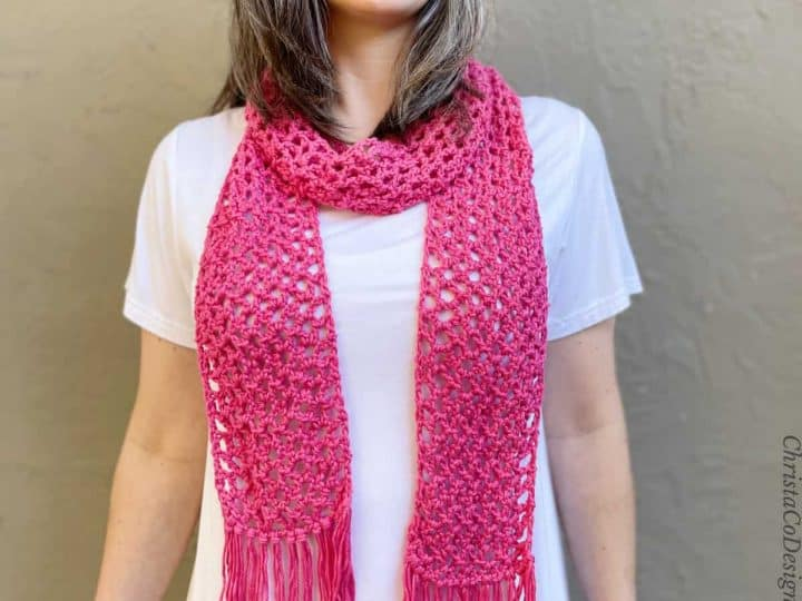 Pink lacy crochet scarf with fringe on woman.