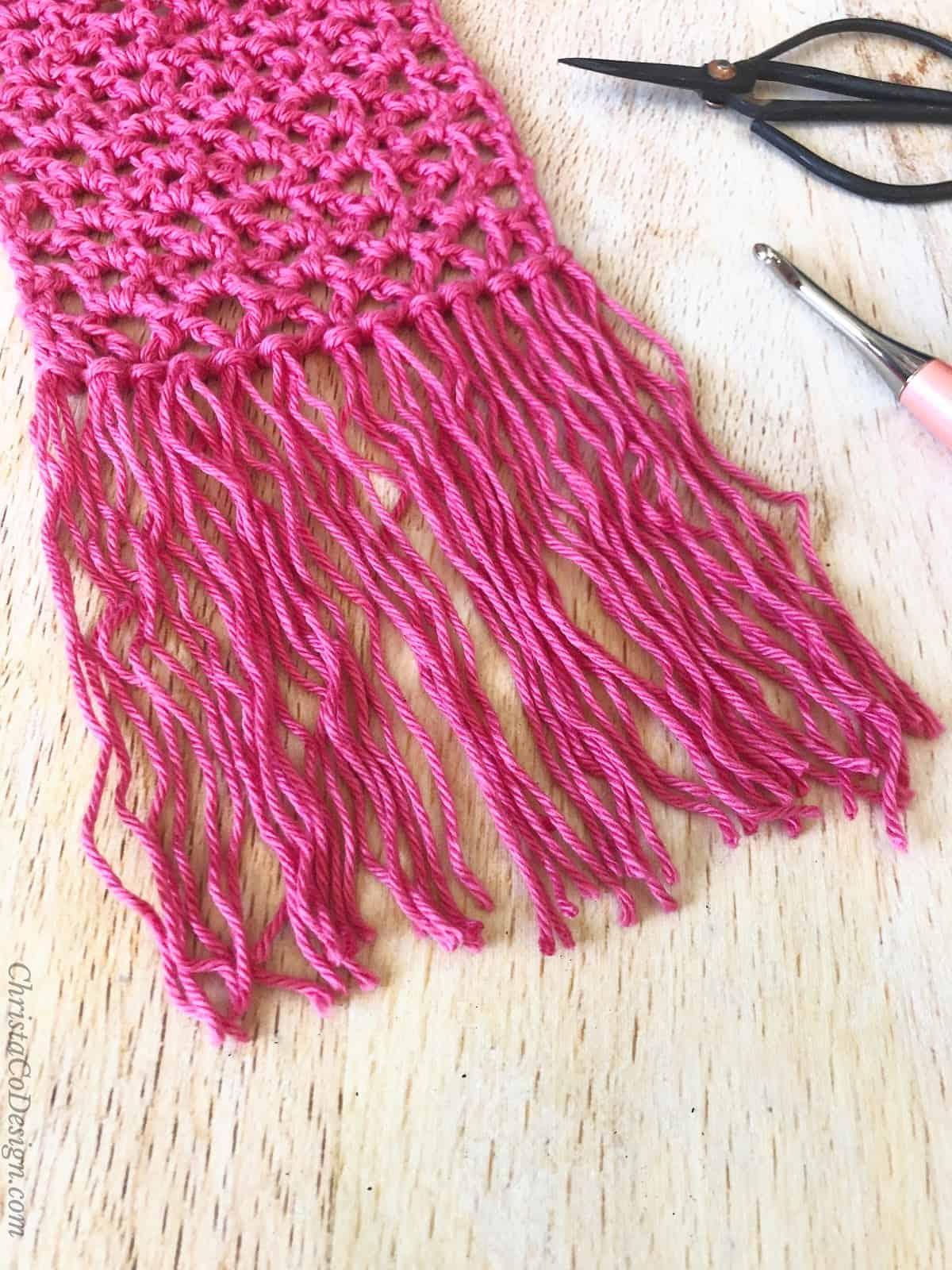 Fringe on end of skinny summer scarf.