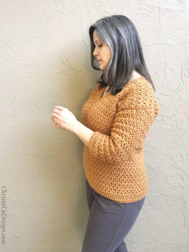 Side view of hip length sweater on model.