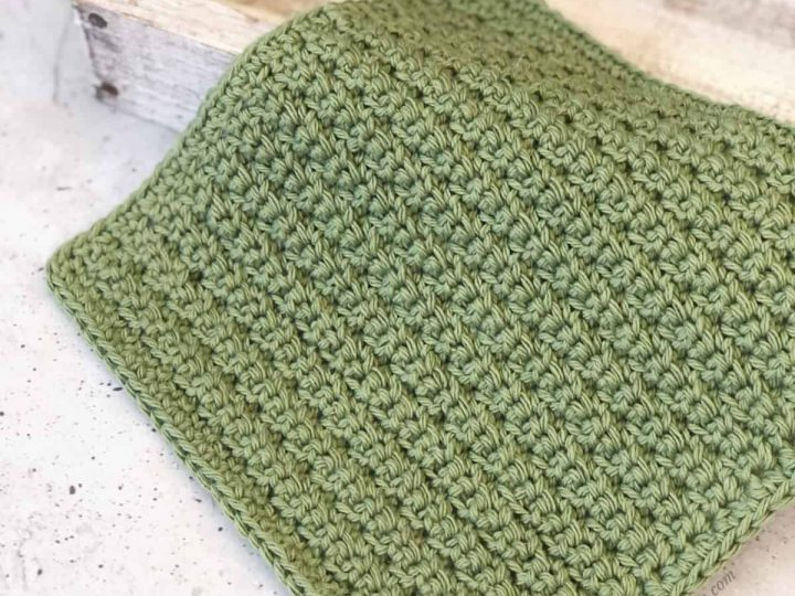 Crochet dishcloth in green on white wood block.