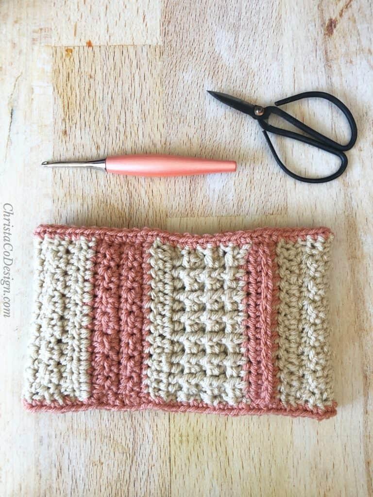 Ear warmer crochet flat with hook and scissors.