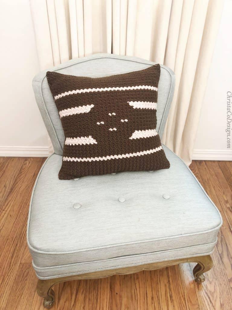 Dark crochet pillow with light contrast design on chair.