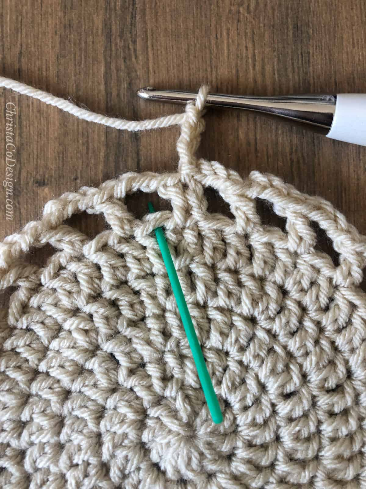 Green yarn needle pointing to stitch.