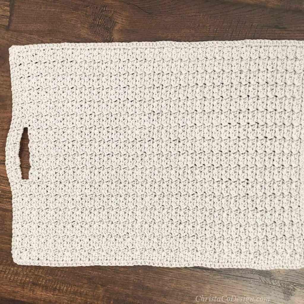 Crochet kitchen towel laid flat with hole for threading and hanging from oven.