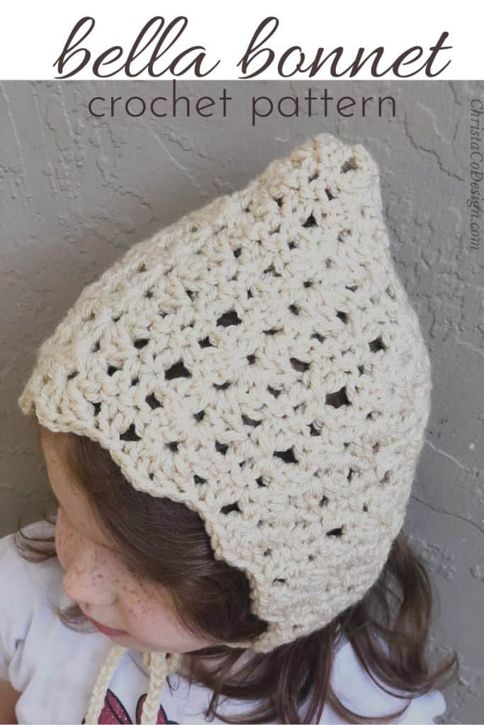 Girl in cream colored crochet bonnet pattern with a pixie point.