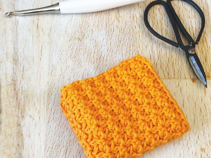 Orange textured Dishcloth pattern folded up on table.