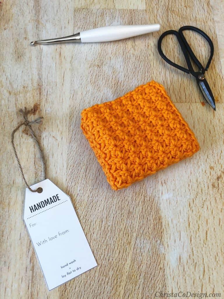 Orange crochet dishcloth folded on with gift tag.