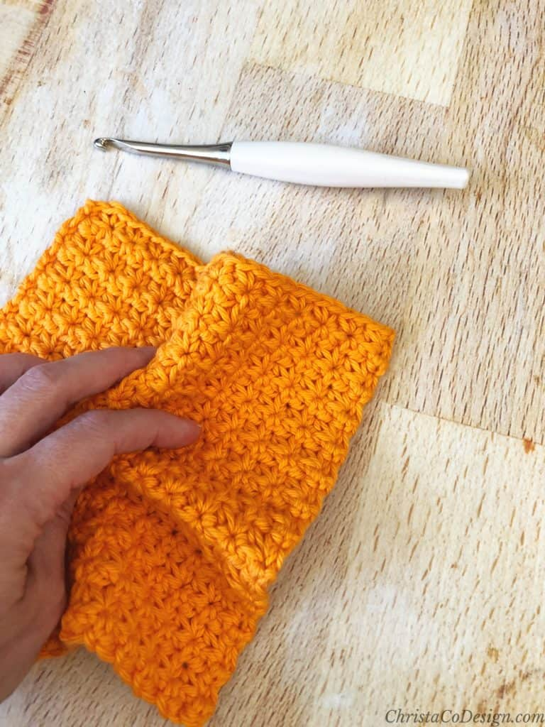 Crochet dishcloth on wood table in woman's hand free pattern.