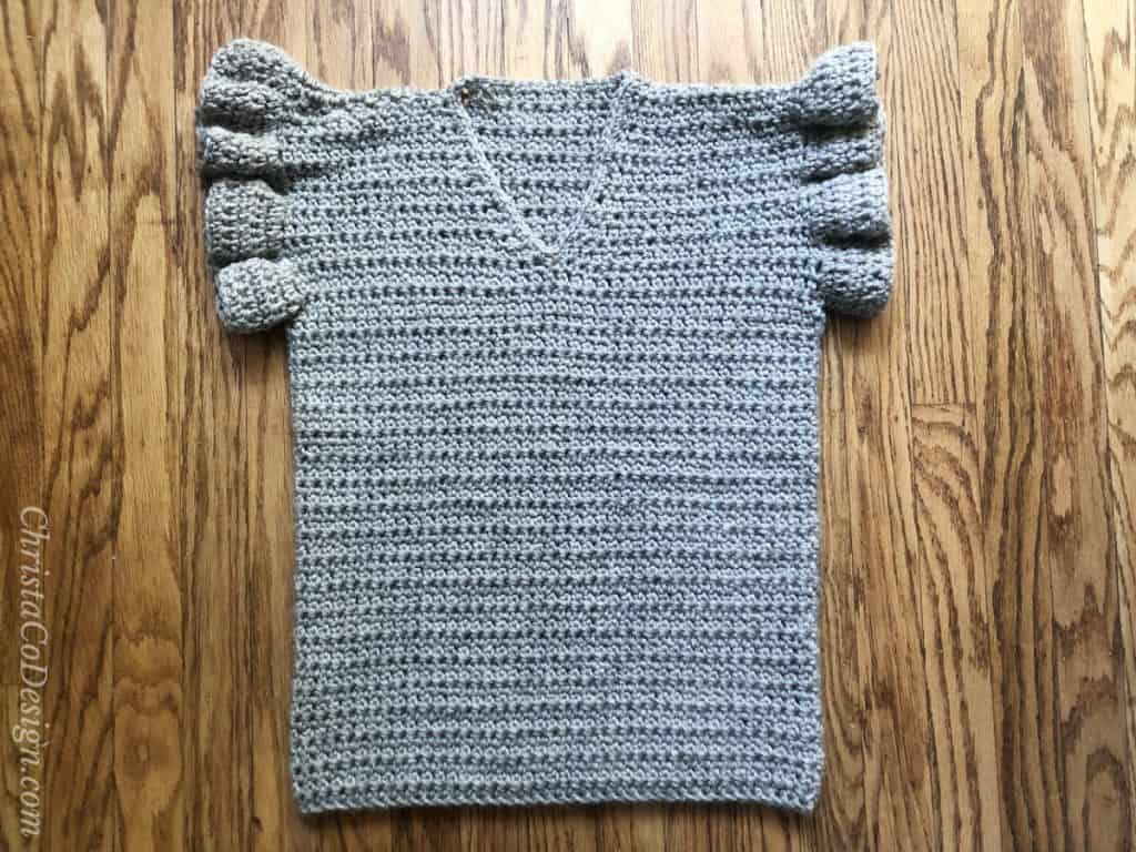 Shallow v-neck free crochet summer top pattern with ruffles on wood background.