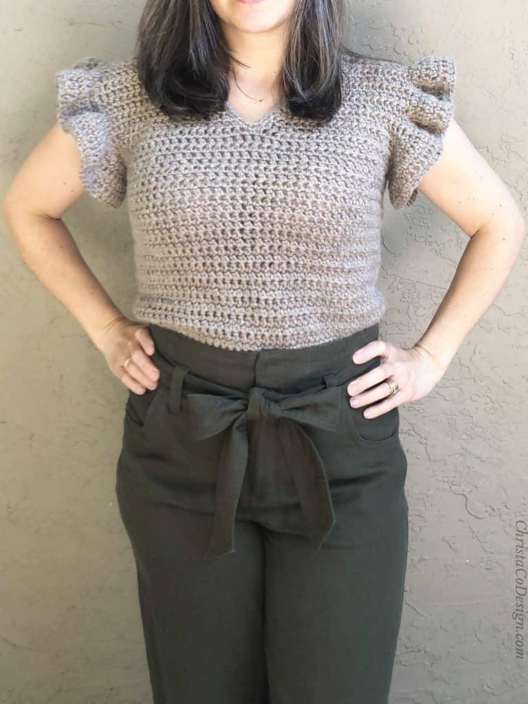 Woman in slim beige  free crochet summer top pattern with ruffle sleeves.