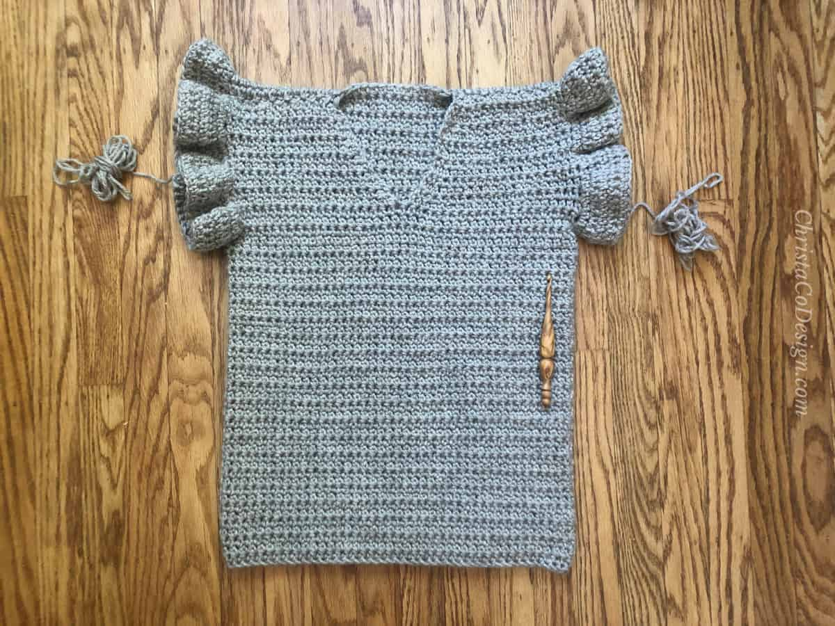 Complete free crochet summer top pattern with ruffles sleeves on wood background.
