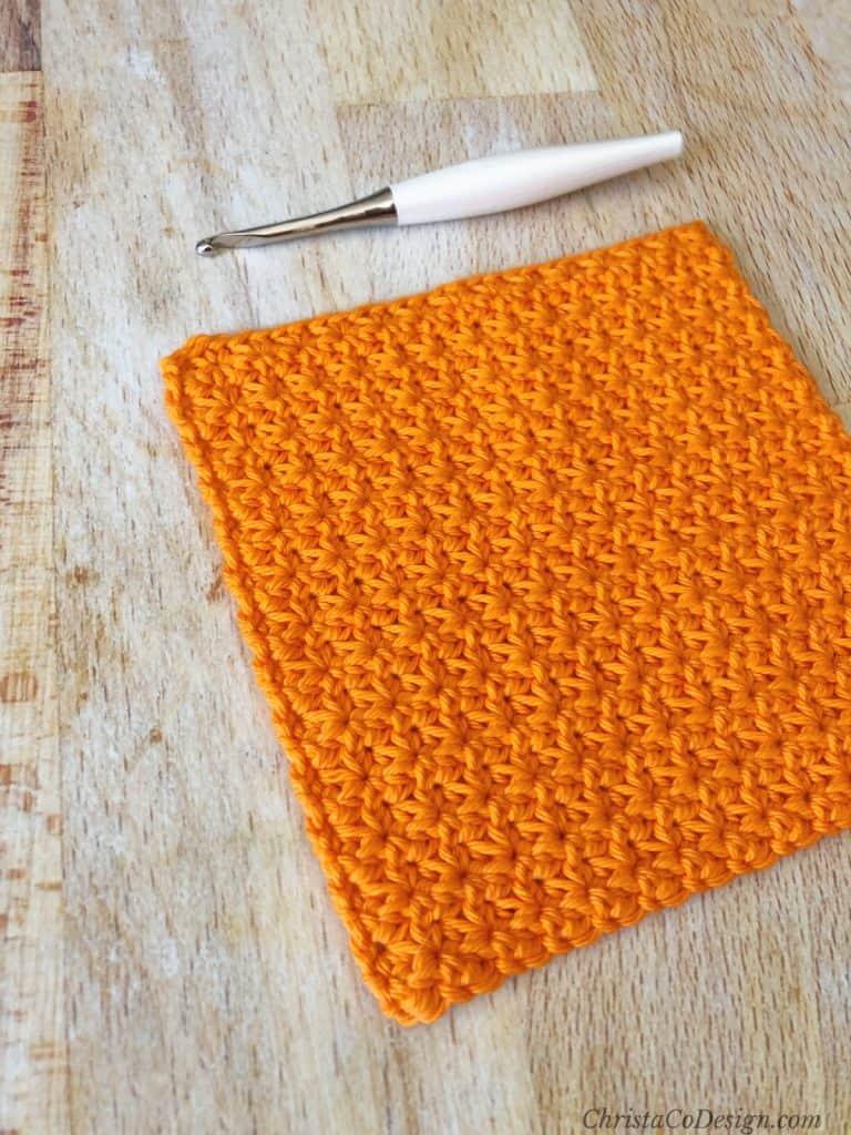 Bright orange crochet dishcloth with textured stitch free crochet pattern.