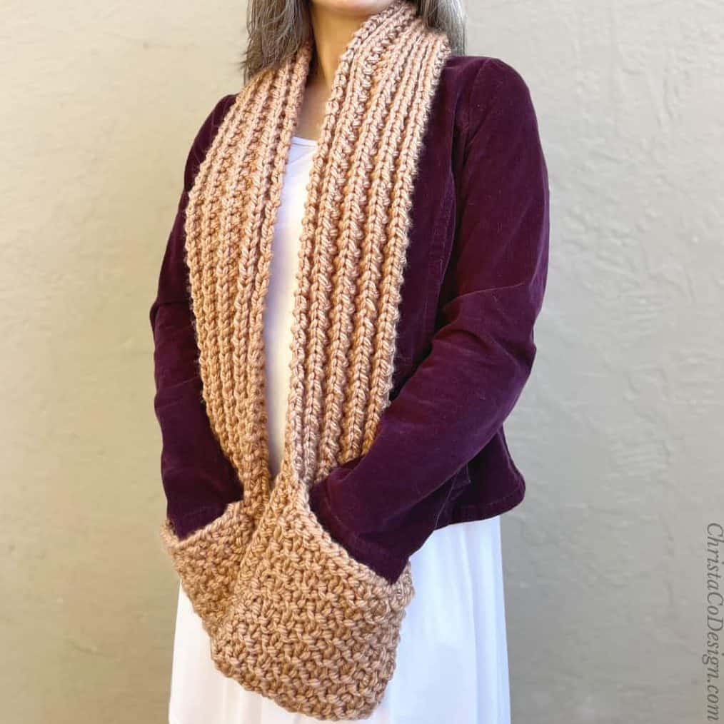Smiling woman in cozy pocket scarf knitting pattern.