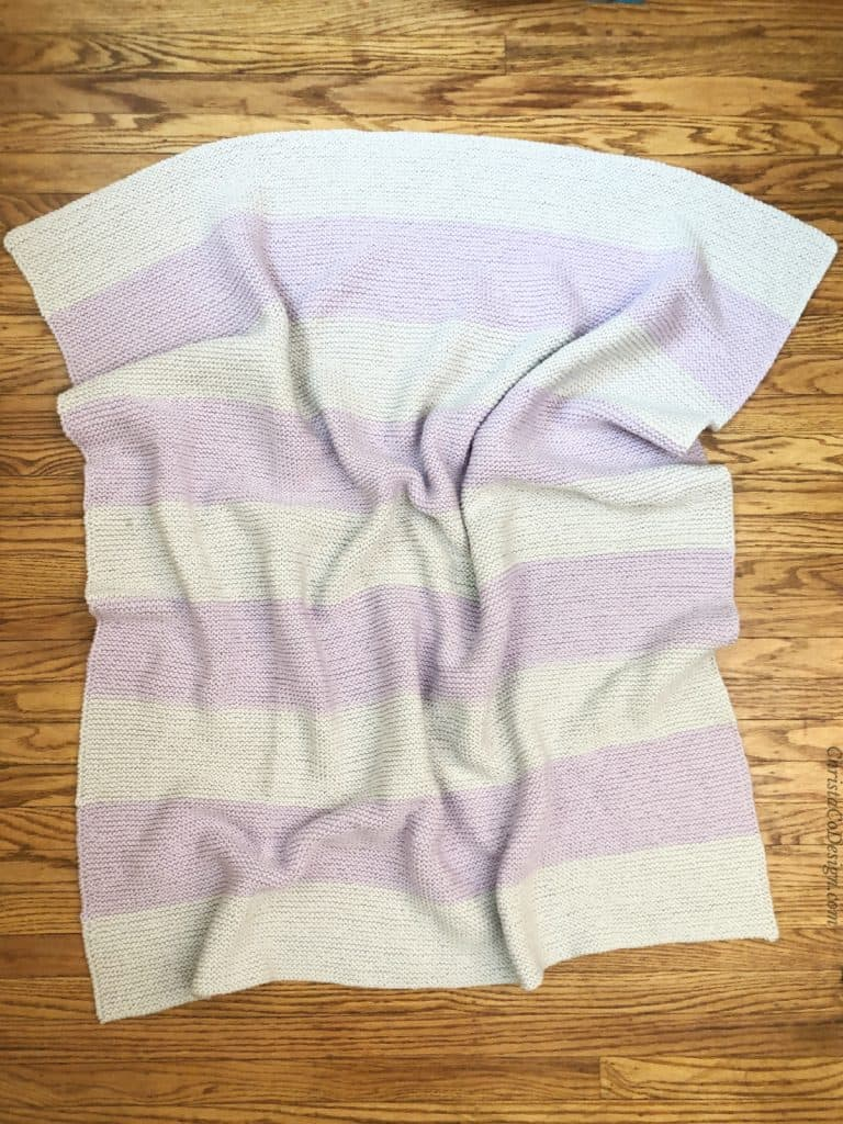 Lavender and grey striped knitted blanket pattern on wood floor.