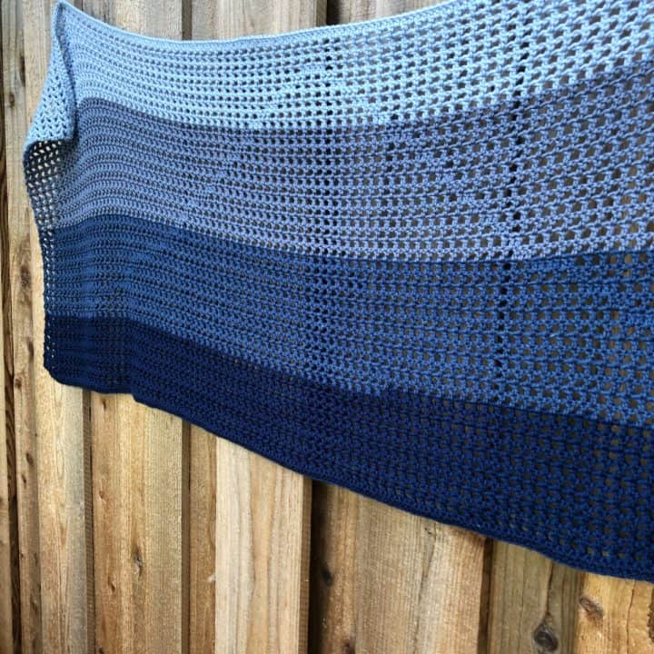 Easy rectangle crochet shawl pattern in double crochets in ombre blues on fence.