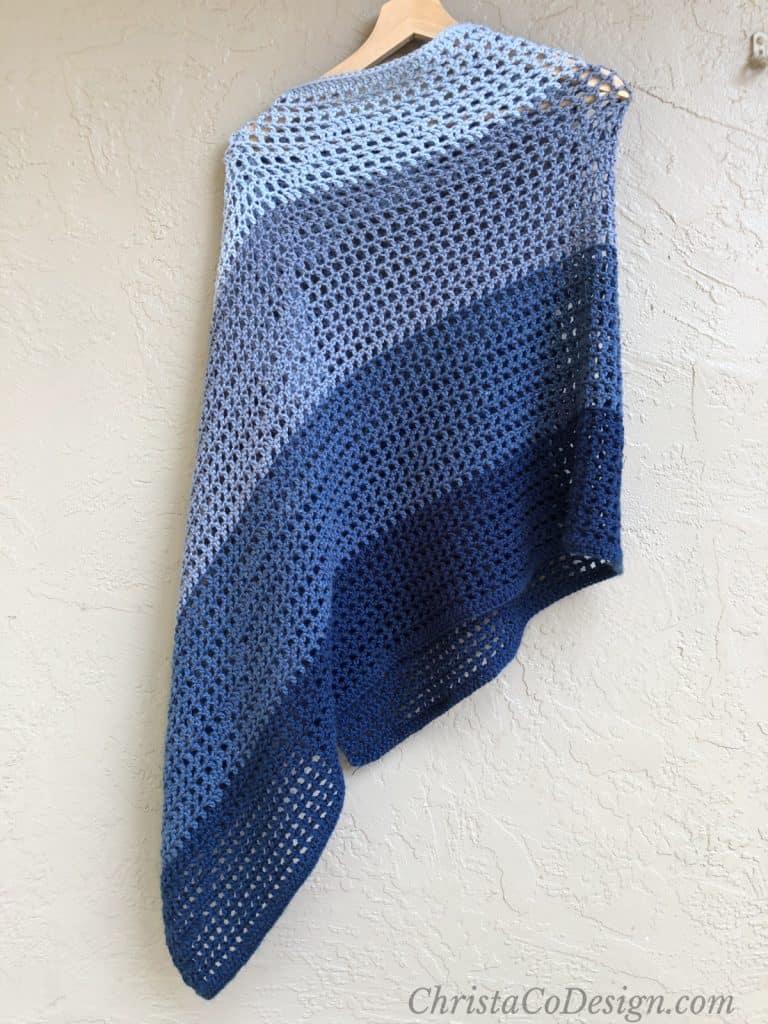 Ombre blue lightweight shawl crochet pattern draped on hanger in front of beige wall.