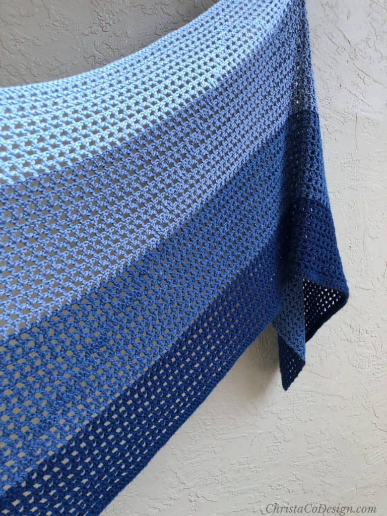 Crochet shawl pattern for summer in open design with blue yarn draped on wall features sloped mountain.