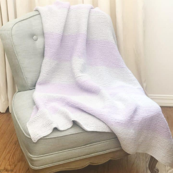 Purple and silver knitted blanket draped on chair in front of cream curtain.