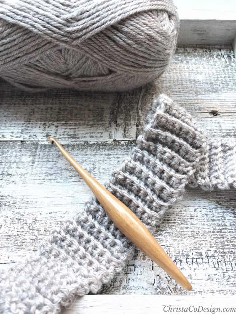 Light wood crochet hook on yarn ribbing in beige.
