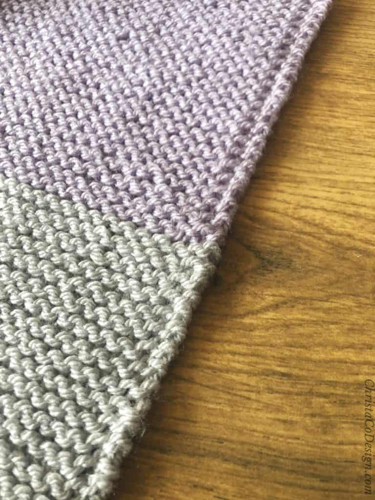 Neat slip one and garter stitch edge in purple and grey.