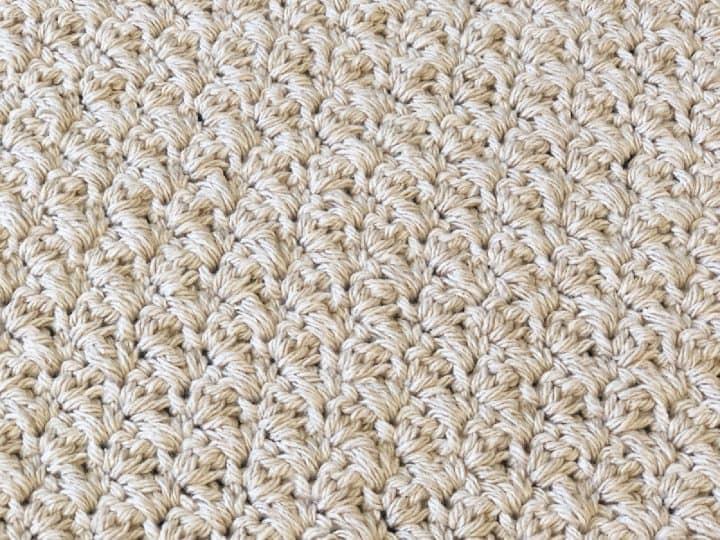 Crochet washcloth in beige cotton yarn, close up.