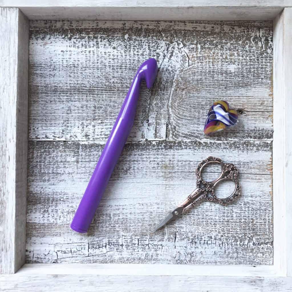 Jumbo purple crochet hook with scissors.