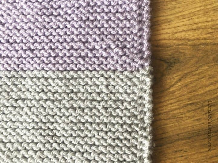 Purple and grey striped blanket with slip one edge.