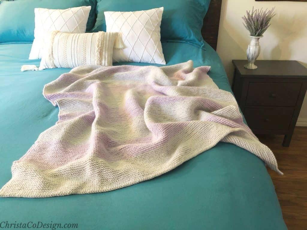 Silver and lavender knit blanket draped on blue bed with white pillows.