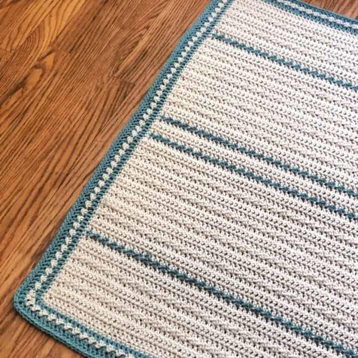 Cream with blue crochet baby blanket on wood floor.