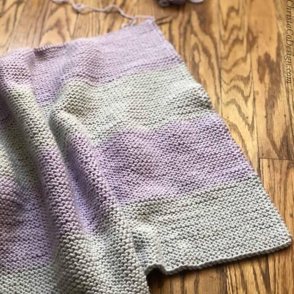Work in progress of grey and lavender knit blanket on wood floor.
