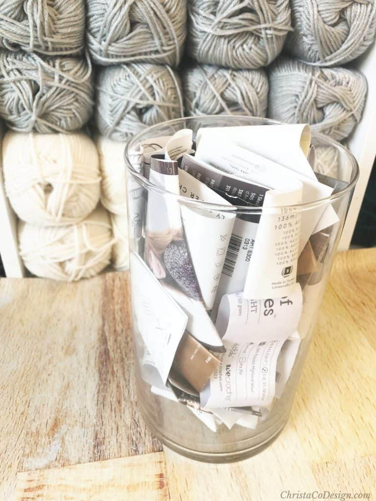 Glass jar filled with yarn labels in front of yarn shelf.