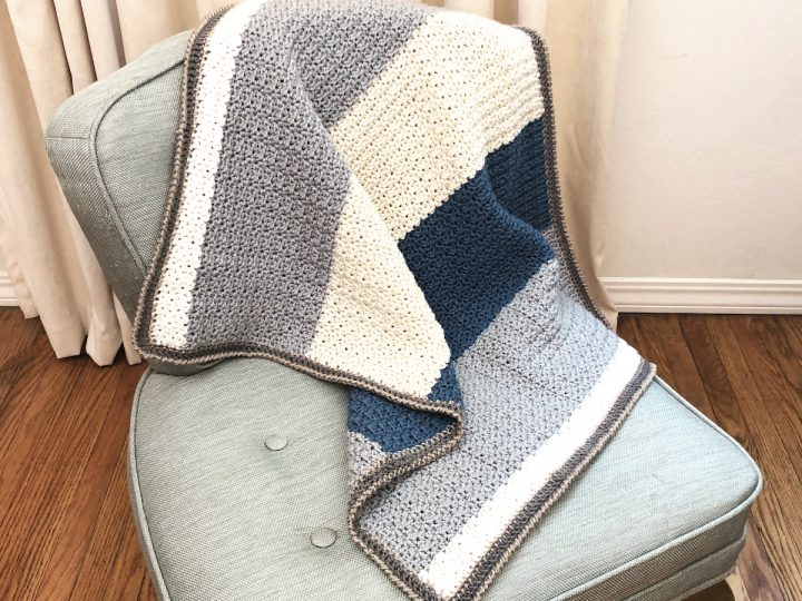 Grey, cream and blue striped crochet baby blanket pattern on chair.