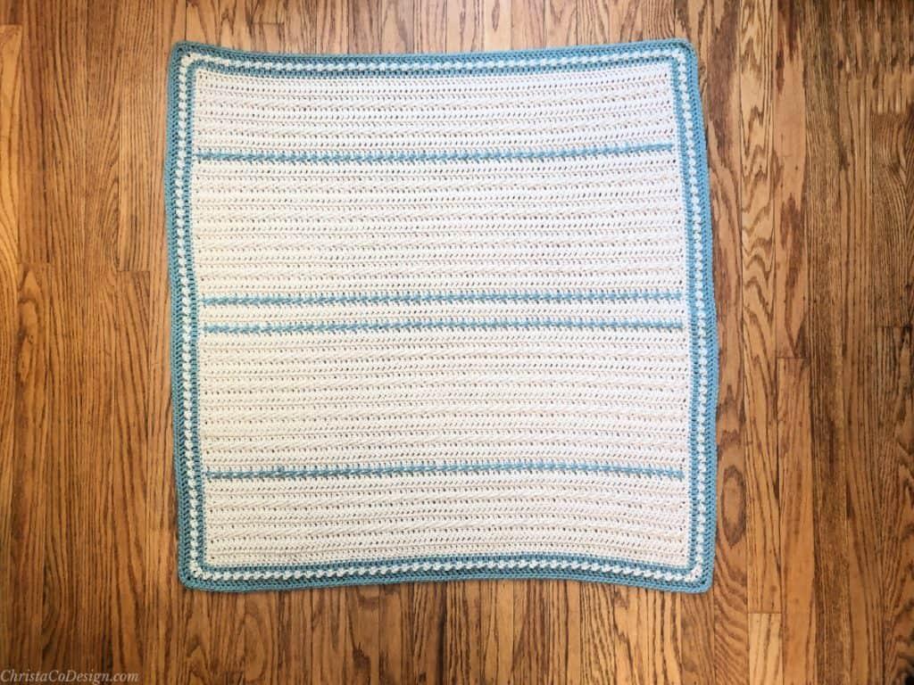 Crochet baby blanket pattern in cream with blue stripes on wood floor.