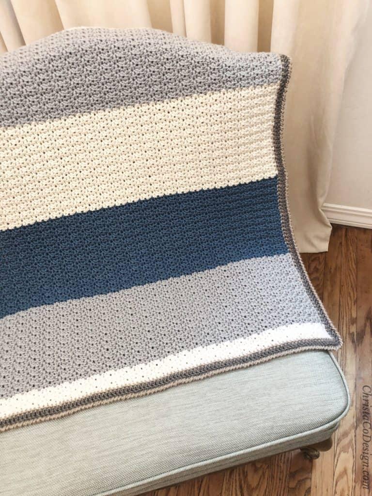 Striped crochet blanket draped open on blue chair.