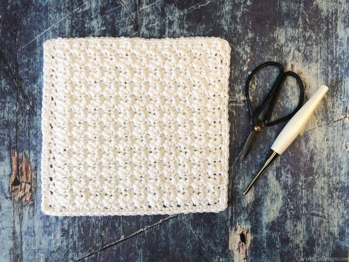 White textured crochet blanket square next to scissors and hook.