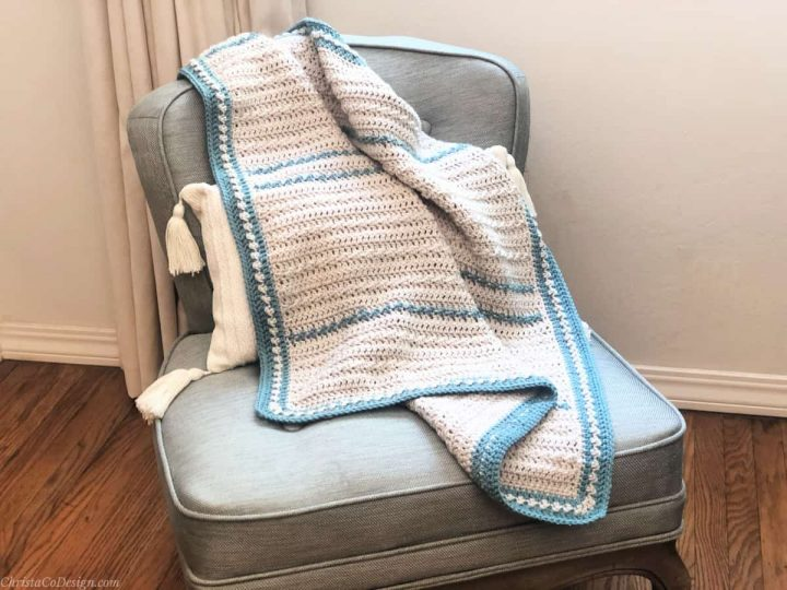 Textured crochet baby blanket on chair in cream and blue.