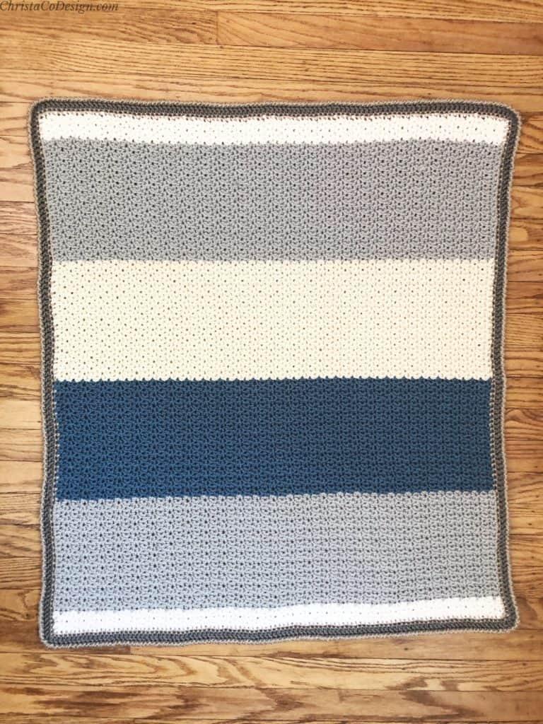 Crochet baby blanket in grey, cream and blue stripes on wood floor.