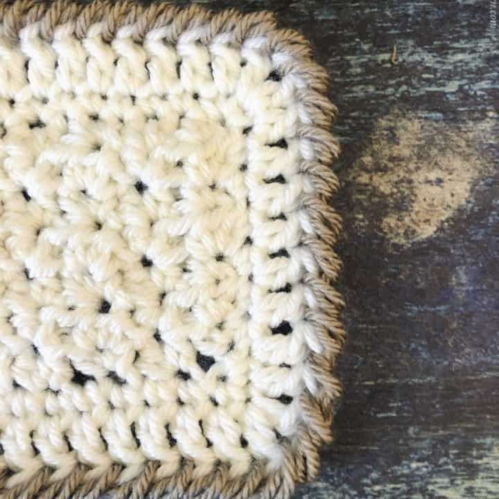 Crochet crab stitch border on blanket square in white and beige.