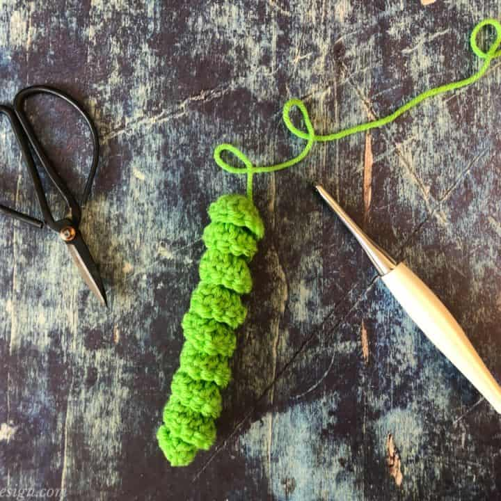 Scissors, green crochet curly Q, white crochet hook.