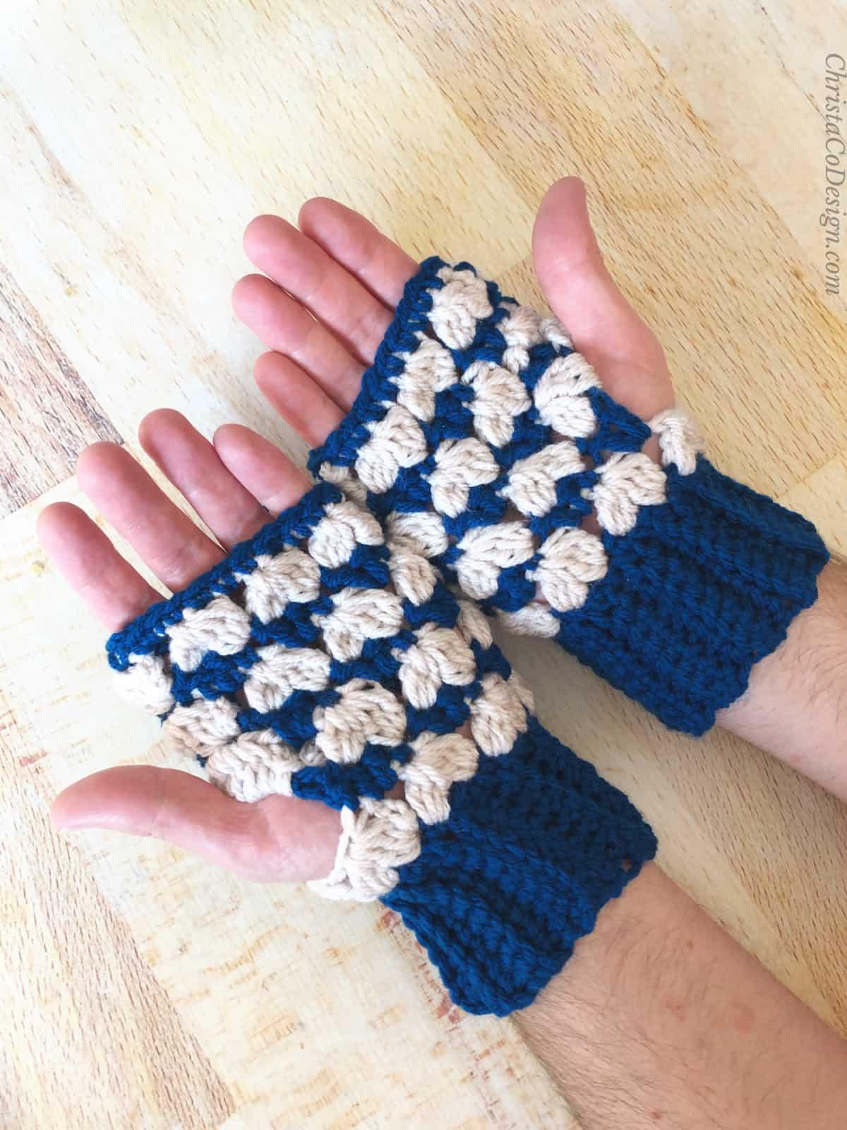 Mens fingerless gloves crochet pattern in blue and cream on light background.
