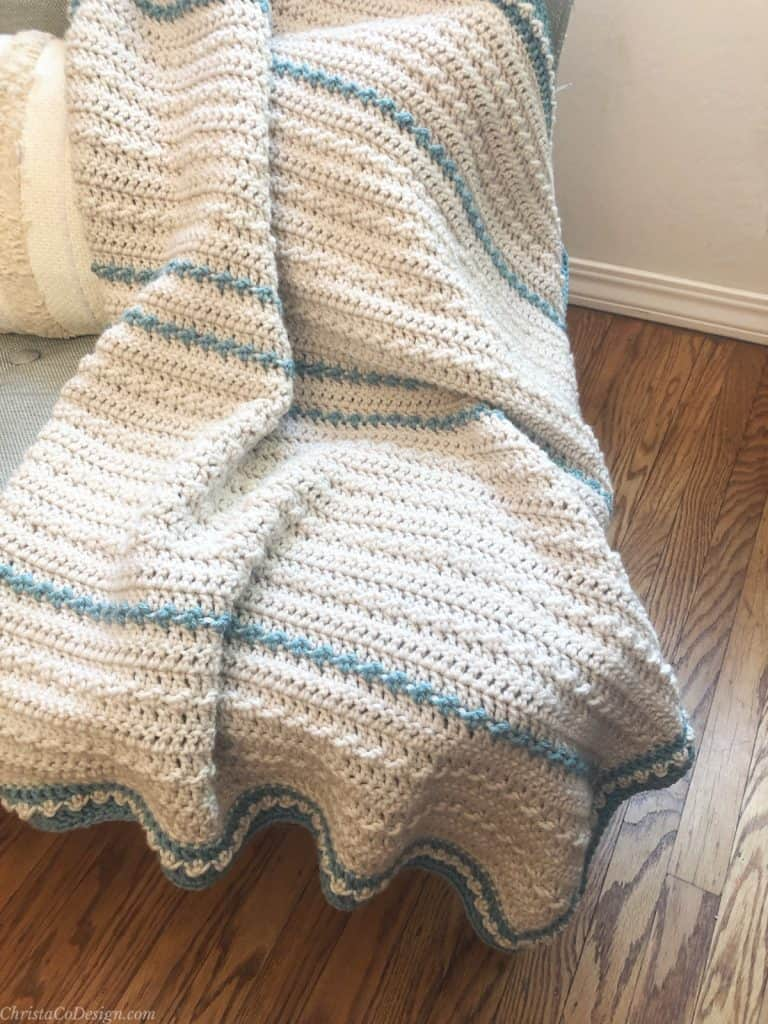 Baby blanket crochet pattern in cream and blue draped on chair.