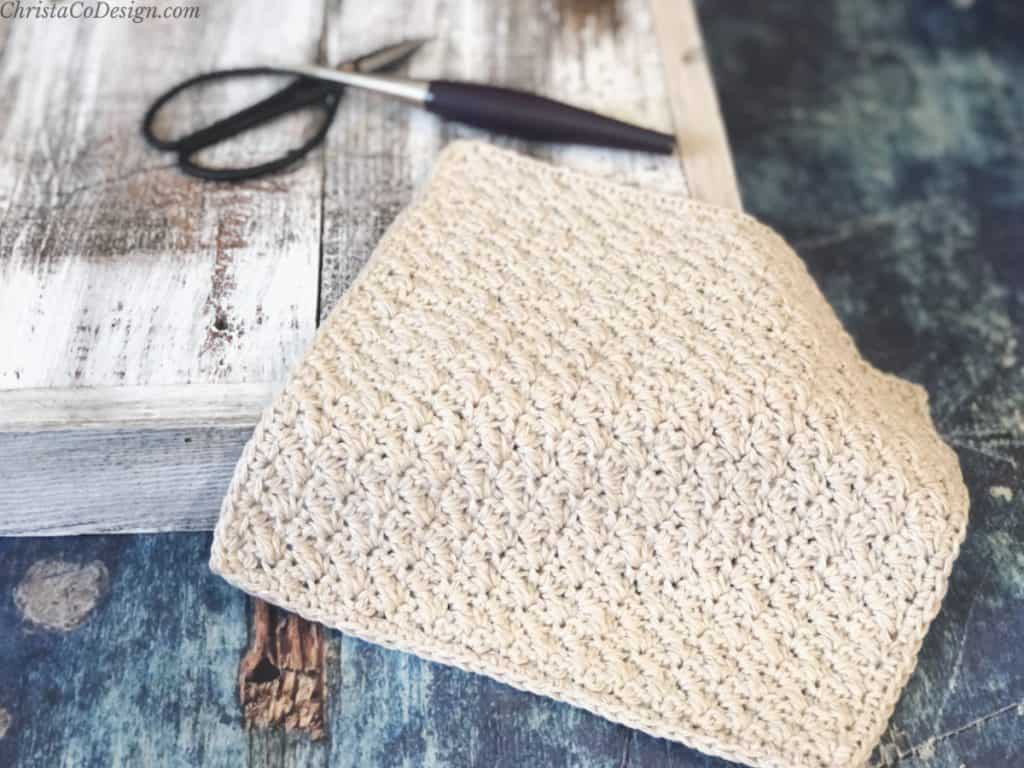 Crochet washcloth pattern easy to make in beige cotton yarn on wood backdrop.